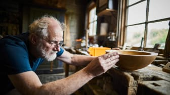 Older man working on a wooden bowl