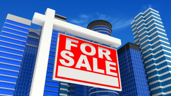 picture of several office buildings with a for sale sign in front of them
