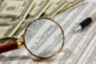 Looking through magnifying glass to the dollars banknotes and financial report