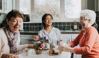 Three older women friends laugh together at a kitchen table.