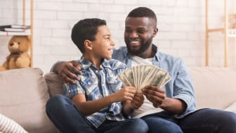picture of a father and son sitting on a couch holding a lot of money