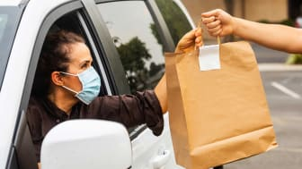 A masked shopper sitting in a car accepts a bag of groceries for pickup