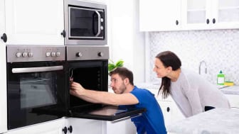 Smiling Young Woman Looking At Technician Fixing Oven In Kitchen