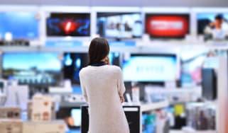 A woman ponders fancy TVs