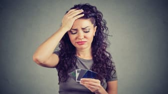 Confused stressed woman looking at too many credit cards