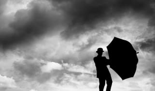 A man holds an umbrella on a cloudy day.