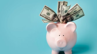 A piggy bank is overflowing with cash.