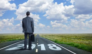 """A businessman stands while holding his briefcase as he looks down a long, straight, rural road that has """"2108"""" painted on it.In the distance, as the road meets the horizon, puffy clouds punct"""
