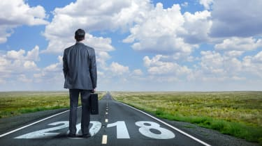 "A businessman stands while holding his briefcase as he looks down a long, straight, rural road that has ""2108"" painted on it.In the distance, as the road meets the horizon, puffy clouds punct"