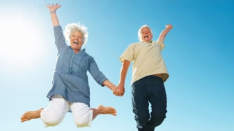 A retired couple jump for joy.