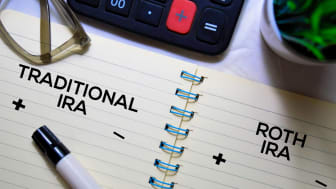 Calculator and planner marked with traditional IRA and Roth IRA