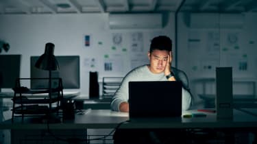 Young businessman looks stressed late at night in the office.