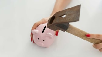 picture of a hammer about to break a piggy bank