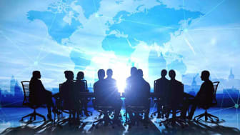 A silhouette of a business meeting up against a blue background showing the world map