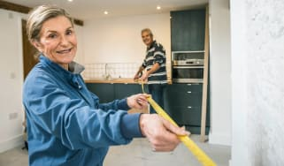 Senior couple measuring space in their home for home improvement