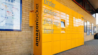 A row of yellow Amazon lockers sits outside a retail establishment