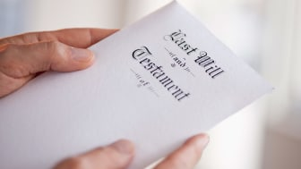 Hands holding a last will and testament document