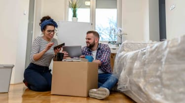 Couple looking at tablet while unpacking