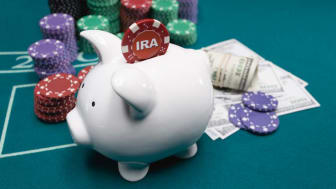 picture of a gambling table with poker chips, cash, and a piggy bank with an IRA poker chip going into it
