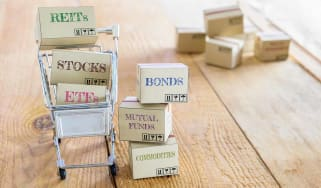 Cartons of financial investment products in a shopping cart i.e REITs, stocks, ETFs, bonds, mutual funds, commodities. A concept of portfolio management with risk diversification for optimal