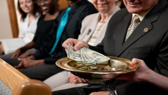 picture of people putting money in collection plate at church