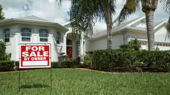 """A Florida home with a """"for sale"""" sign in front of it."""