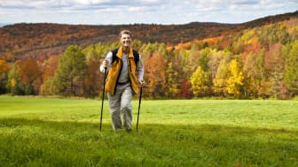 Senior man hiking in the hills of Vermont with autumn colors behind him