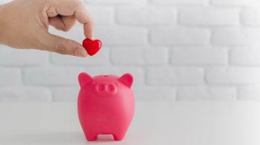 A hand deposits a heart into a pink piggy bank.