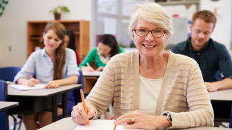 Happy senior woman at an adult education class looking to camera