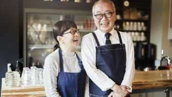 The owners of a bakery smile and laugh.