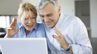A happy senior couple making a video call on a laptop