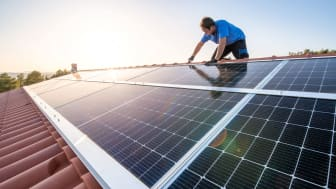 A person installs solar panels on a house.