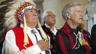 Two senior men, one wearing Native American clothing, say the Pledge of Allegiance