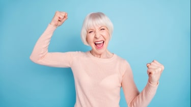 A happy woman pumps her fist in the air.