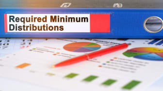 """picture of a binder label """"required minimum distributions"""" next to some printed charts"""