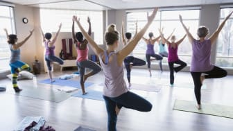 Women practicing tree pose in yoga class