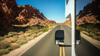 The driver's outside mirror is pictured as an RV rolls on a mountain road