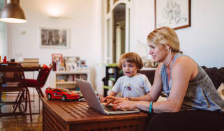 picture of a mother working on a computer while her young child watches