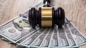 picture of a judge's gavel laying on one-hundred dollar bills
