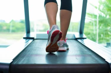 Close up womans legs in pink sneakers on a. Treadmill in the gym.