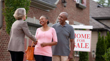 Senior couple buying or selling a house shaking hands with Realtor