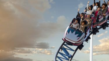 Business people riding roller coaster