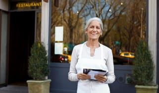 mature woman small business owner outside her restaurant with menus