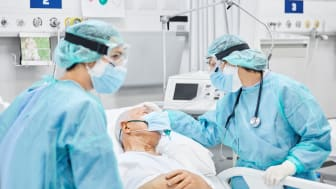 Doctors help a patient suffering from COVID-19
