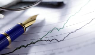 A blue and gold fountain pen and a pair of eyeglasses sit on top of a chart showing diverging trend in sales growth or stock market performance.Image is shot with a very shallow depth of fiel