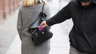 picture of man stealing something from a woman's purse