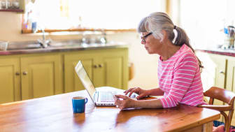 A senior woman on her laptop computer in her kitchen