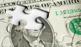 A puzzle of a dollar bill has a missing piece.