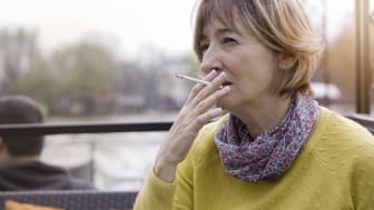 Mature woman sittingin cafe outdoors and smoking a cigarette.