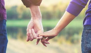 A couple link their pinky fingers together.